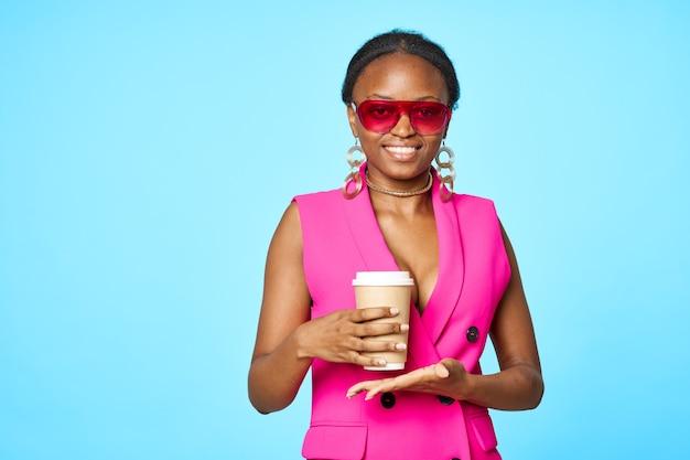 Apparence africaine portant des lunettes de soleil café dans les mains fond bleu