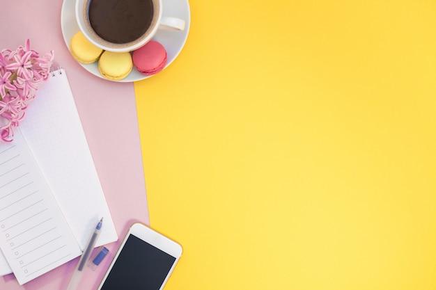 Appartement créatif poser avec une tasse de café et des macarons