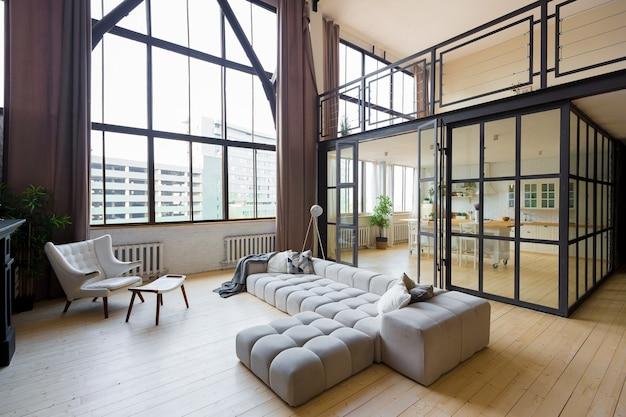 Appartement à deux niveaux au design moderne et branché avec de grandes fenêtres hautes. l'élégant salon et la cuisine aux couleurs vives sont déshabillés par une cloison en verre. chambre au deuxième étage.