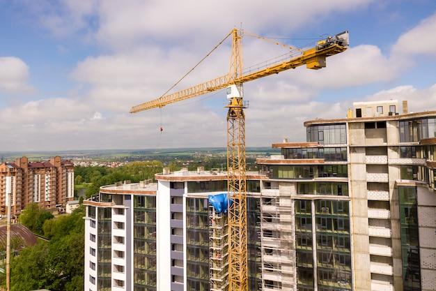 Appartement ou immeuble de bureaux en construction. murs en briques, fenêtres en verre, échafaudages et piliers de soutien en béton. grue à tour sur l'espace de copie de ciel bleu lumineux