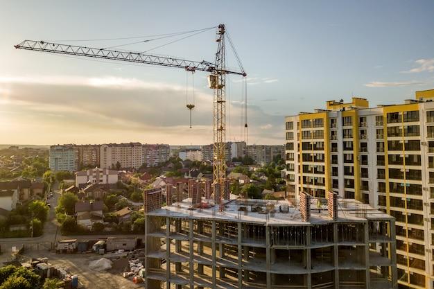 Appartement ou immeuble de bureaux en construction. murs en briques, fenêtres en verre, échafaudages et piliers de soutien en béton. grue à tour sur fond d'espace de copie de ciel bleu clair.