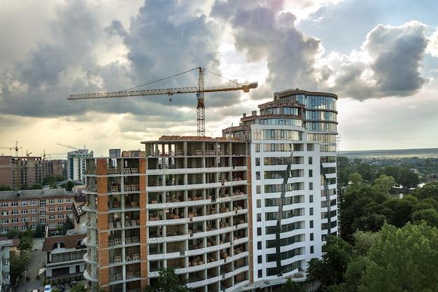 Appartement ou immeuble de bureaux en construction. murs en briques, fenêtres en verre, échafaudages et piliers de soutien en béton.
