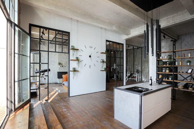 Appartement de luxe dans un style loft aux couleurs sombres. coin cuisine moderne et élégant avec îlot