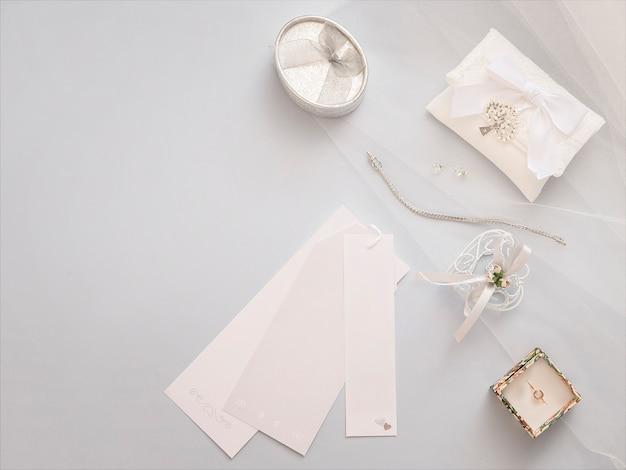 Appartement minimal poser avec des accessoires de mariage sur fond de voile léger.