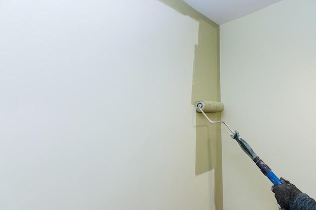 Appartement de peinture, rénover avec un pinceau à rouleau de couleur, peindre le mur de surface.