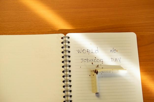 Appartement posé, cigarettes et inscription journée mondiale sans tabac écrite dans un cahier