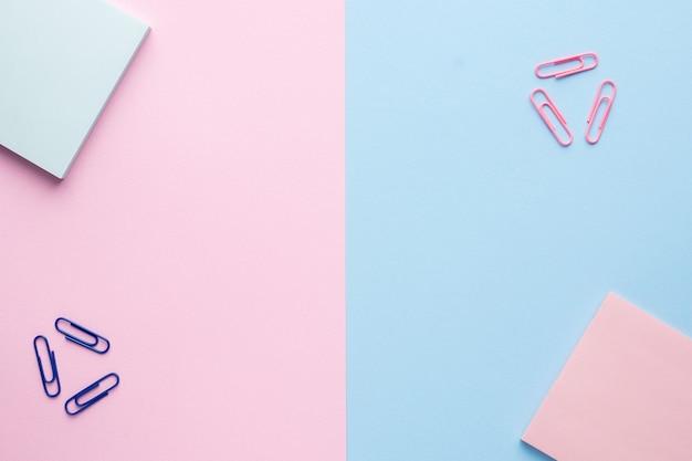 Appartement posé sur un fond rose et bleu pastel avec un trombone du bloc-notes