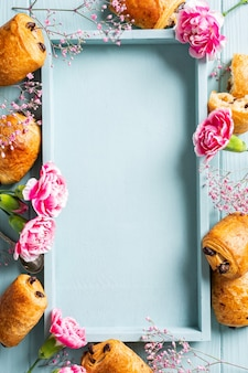 Appartement de vacances avec mini pain de croissants frais avec des fleurs de chocolat et d'oeillet sur une surface bleu turquoise. vue de dessus. copier l'espace