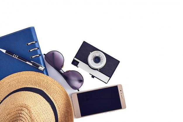 Appartement de vacances poser ensemble. chapeau de paille et téléphone, lunettes de soleil et appareil photo.