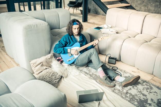 Appartements élégants. jeune artiste calme assis sur le sol et penché sur de nouvelles compositions tout en ayant ouvert un ordinateur portable à proximité