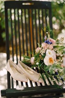 Appartements nuptiales recouverts de strass sur une chaise à côté d'un bouquet de fleurs