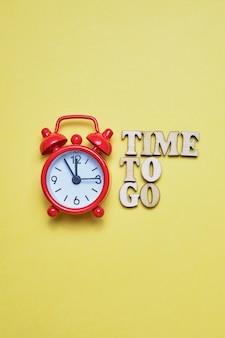 Un appel abstrait à l'action - il est temps de partir. lettres en bois à côté de l'horloge rouge