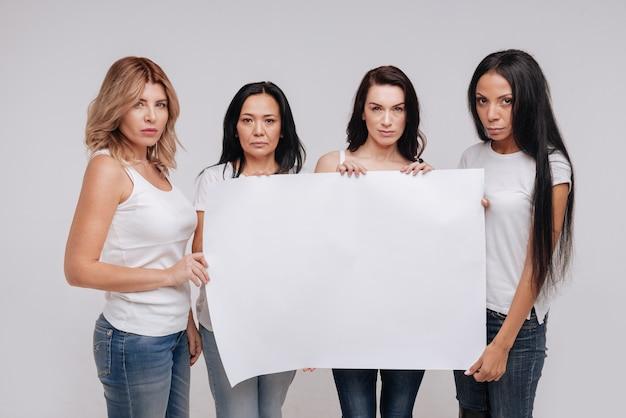 Appel à l'action. sérieuses dames diverses indépendantes s'unissant pour une cause tout en tenant une affiche vierge de cochon et en posant dans des vêtements similaires