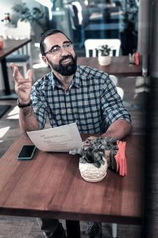 Appel au serveur. homme aux cheveux noirs rayonnant portant des lunettes levant sa main appelant le serveur après avoir choisi le plat