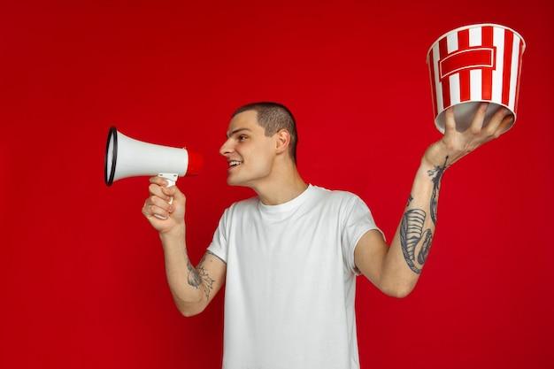 Appel avec haut-parleur. portrait de jeune homme caucasien sur mur rouge. beau modèle masculin avec pop-corn. concept d'émotions humaines, d'expression faciale, de vente, de publicité, de cinéma et de divertissement.