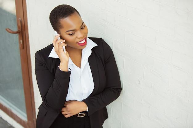 Appel important. femme d'affaires afro-américaine en tenue de bureau souriante, a l'air confiante et heureuse, occupée. concept de finance, d'entreprise, d'égalité et de droits de l'homme. belle jeune femme modèle, réussie.
