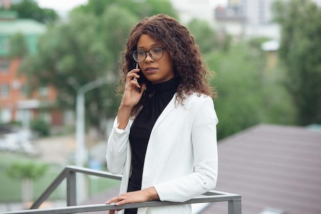 Appel important. femme d'affaires afro-américaine en tenue de bureau souriante, a l'air confiante et sérieuse, occupée. concept de finance, d'entreprise, d'égalité et de droits de l'homme. belle jeune mannequin, réussie.