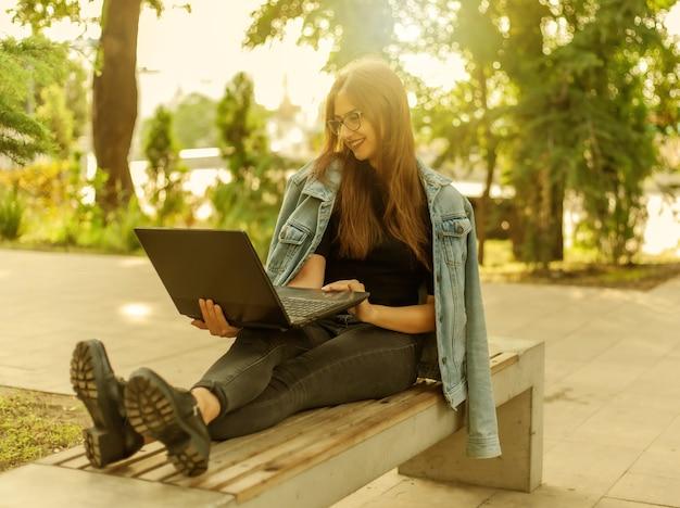 Appel en ligne. apprentissage à distance. une jeune étudiante dans une veste en jean et des lunettes regarde un écran d'ordinateur portable alors qu'elle était assise sur un banc dans un parc