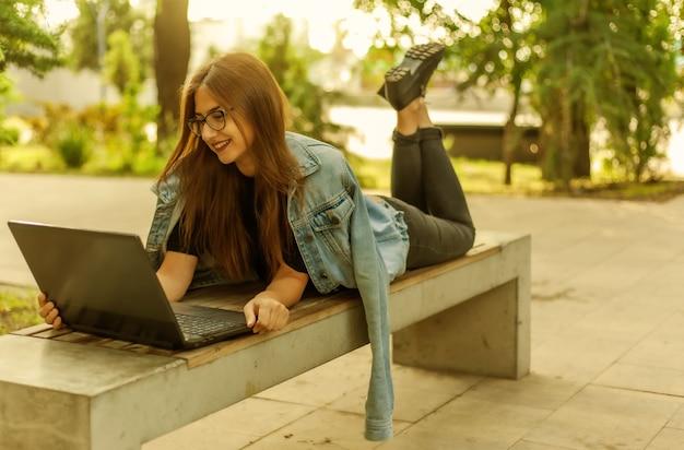 Appel en ligne. apprentissage à distance. une jeune étudiante dans une veste en jean et des lunettes regarde un écran d'ordinateur portable en position allongée sur un banc dans un parc