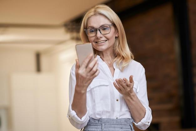 Appel en ligne belle femme âgée en tenue décontractée souriant et parlant tout en faisant un appel vidéo
