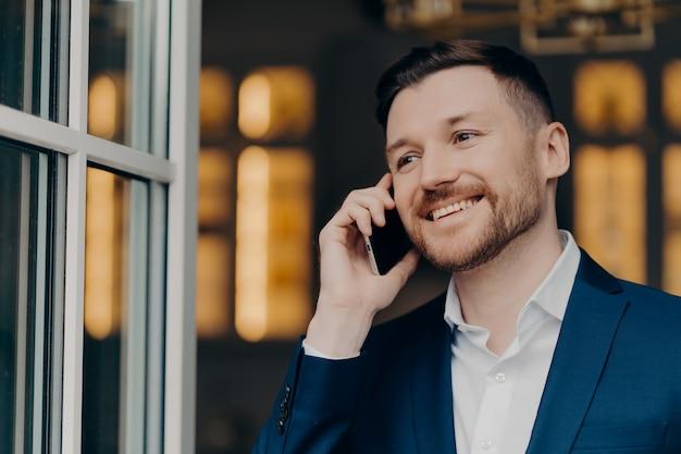Appel mobile. beau directeur exécutif masculin avec des poils a une conversation téléphonique aime la communication moderne sourit joyeusement regarde pensivement dans la chemise blanche et le costume élégant