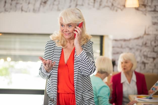 Un appel téléphonique. une femme senior blonde parlant au téléphone et ayant l'air excitée