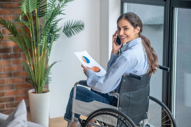 Appel téléphonique. une jolie fille sur un fauteuil roulant parlant au téléphone et souriant