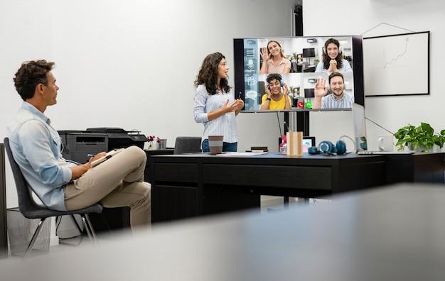 Appel vidéo au bureau avec des collègues multiraciaux travaillant à domicile