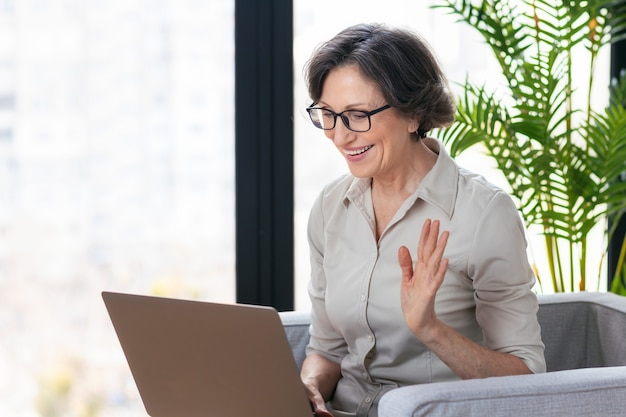 Appel vidéo, concept de travail à distance. belle femme d'affaires d'âge caucasien utilisant un ordinateur portable pour la communication en ligne via internet, assise sur un fauteuil au bureau ou à la maison