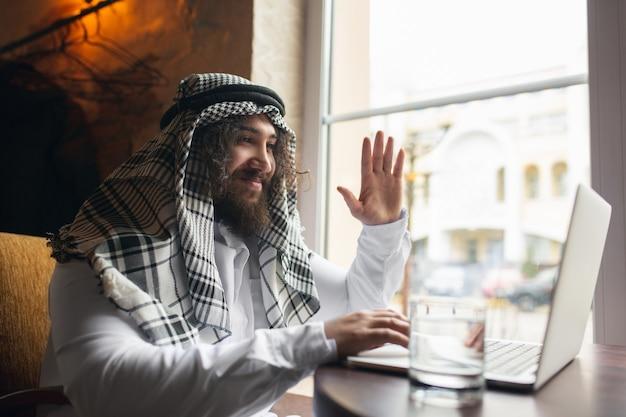 Appel vidéo. homme d'affaires arabe travaillant au bureau, centre d'affaires utilisant un appareil, gadget. mode de vie saoudien moderne. l'homme en tenue traditionnelle et écharpe a l'air confiant, occupé, beau. ethnicité, finances.