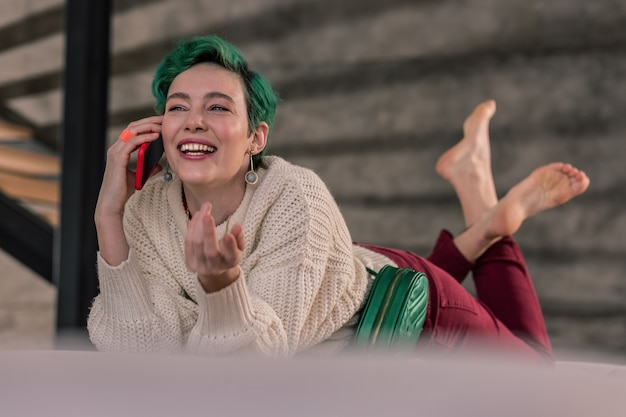 Appeler un ami. célèbre créatrice de mode aux cheveux verts appelant son amie et l'invitant à dîner