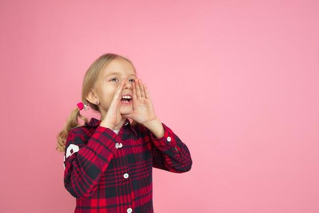 Appeler, crier. portrait de petite fille caucasienne sur mur rose. beau modèle féminin aux cheveux blonds. concept d'émotions humaines, expression faciale, ventes, publicité, jeunesse, enfance.