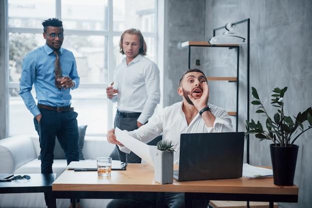 Appeler un employé. les chefs d'équipe ont une bonne humeur au bureau avec une fenêtre à l'arrière-plan