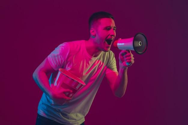 Appeler pour vendre, crier. portrait d'un homme caucasien isolé sur un mur rose-violet à la lumière du néon. modèle masculin avec appareils. concept d'émotions humaines, expression faciale,