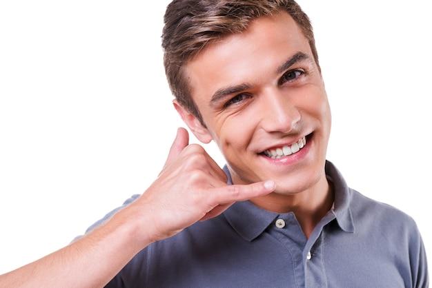 Appelle-moi! heureux jeune homme gesticulant téléphone portable près du visage et souriant en se tenant debout isolé sur fond blanc