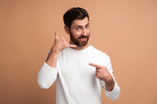 Appelle-moi. portrait d'un bel homme gai debout avec un geste de la main téléphonique et souriant à la caméra, flirtant offrant de contacter par téléphone. studio shot isolé sur fond beige