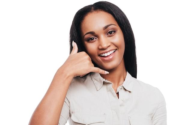 Appelle-moi! souriante jeune femme africaine gesticulant un téléphone portable près de son visage et souriant en se tenant debout sur fond blanc