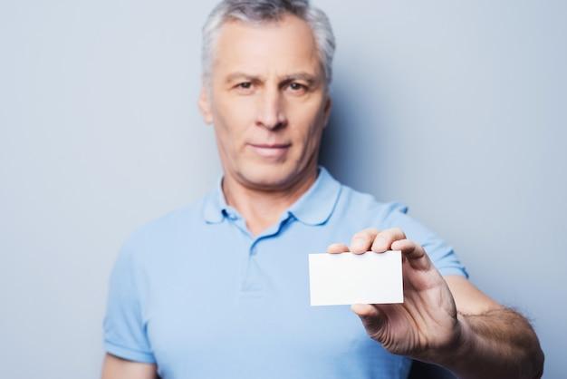 Appelle ce numéro! bel homme senior étirant une carte de visite et souriant en se tenant debout sur fond gris