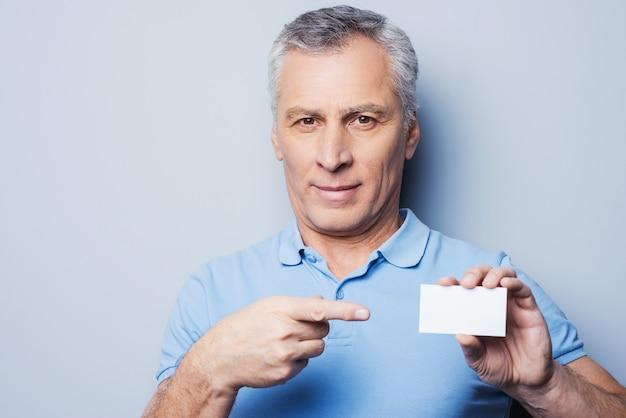 Appelle ce numéro! bel homme senior pointant sur une carte de visite et souriant en se tenant debout sur fond gris