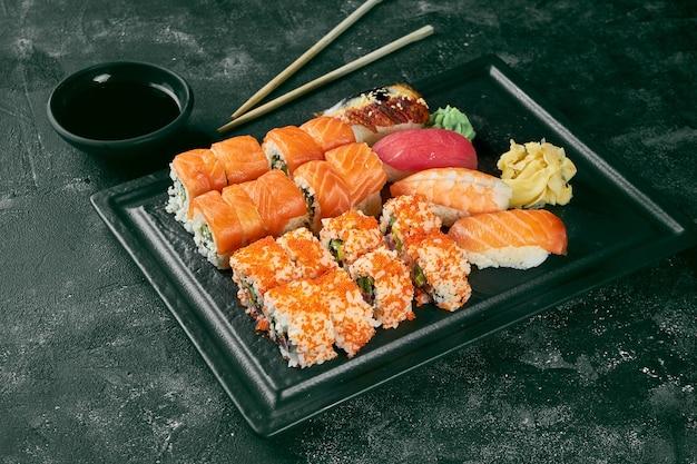 Un appétissant ensemble de sushis composé de divers uramaki au saumon, avocat et caviar tobiko et nigiri. cuisine traditionnelle japonaise. livraison de nourriture. fond noir