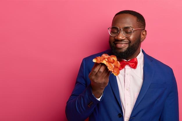 Appétissant de malbouffe. heureux homme afro-américain à la peau sombre sent la délicieuse pizza, ayant faim après le travail, porte un costume bleu formel, un nœud papillon rouge, une chemise blanche