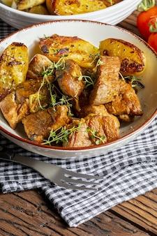 Appétissant ragoût de viande de filet de porc cuit au wok coupé en cubes avec pommes de terre rôties et dorées aspect maison