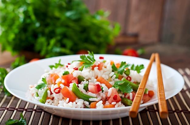 Appétissant riz sain avec des légumes en plaque blanche sur une surface en bois