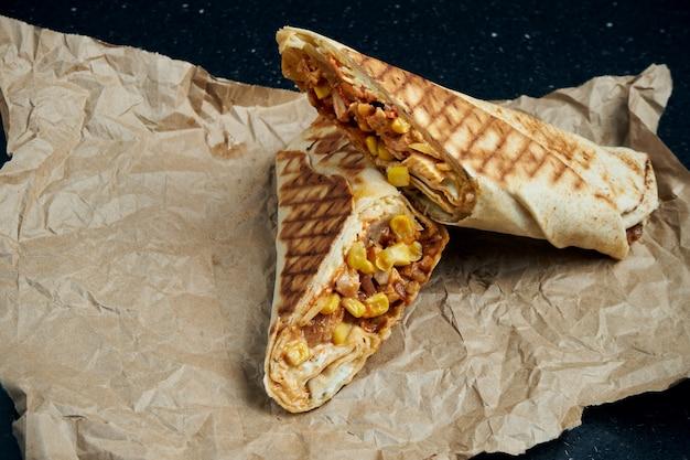 Appétissant rouleau de shawarma avec de la viande, de la salade et de la sauce maison dans un mince pain pita sur du papier kraft sur un tableau noir. cuisine orientale. kebab en tranches avec de la viande grillée.