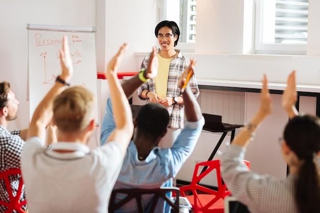 Applaudir. des jeunes satisfaits visitant un séminaire de développement personnel et applaudissant au conférencier professionnel