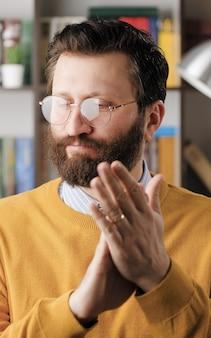 Applaudissements sarcastiques de l'homme. un homme barbu sombre et sceptique dans des verres dans un bureau ou un appartement frappe à contrecœur ses paumes pour créer de faux applaudissements. vue rapprochée