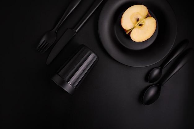 Apple sur une assiette noire, couverts noirs, verre noir sur fond noir, vue de dessus
