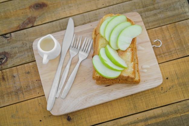 Apple avec du pain servi sur plaque de bois