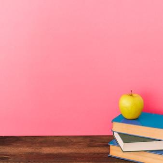 Apple et livres près du mur rose
