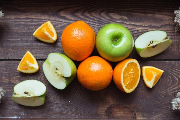 Apple et orange sur le plateau en bois